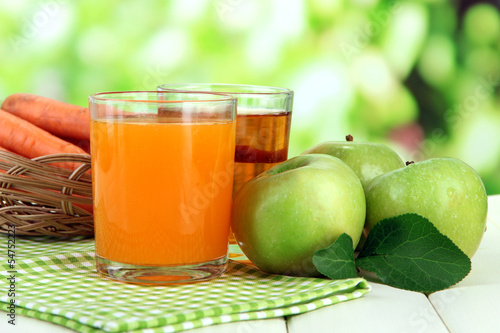Glasses of juice, apples and carrots