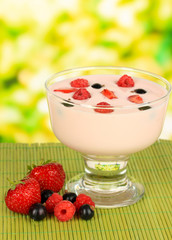 Delicious yogurt with fruit on table on bright background