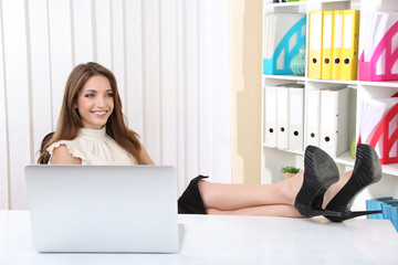 Businesswoman resting at his office with her shoes on table