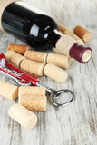 Corkscrew with wine corks and bottle of wine
