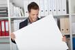 lächelnder mann im büro hält weißes plakat