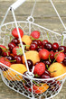 Mix of summer fruits and berries in wire basket