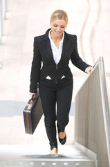 Businesswoman walking upstairs with briefase