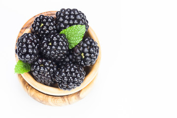 Blackberries in olive wood bowl on white background  .