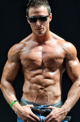Handsome, muscular shirtless muscle man isolated on black