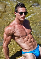 Young muscle man outdoors in water showing muscular body