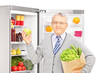 Smiling mature man holding a paper bag next to a refrigerator fu