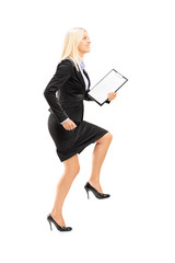 Full length portrait of a young businesswoman doing a huge step