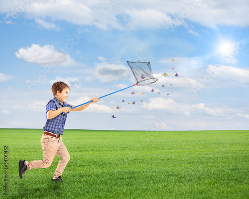Child running and catching butterflies with net on a field