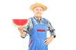 Smiling farmer in dungarees holding a slice of watermelon