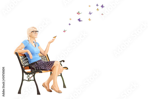 Young female sitting on a wooden bench and looking at colorful b