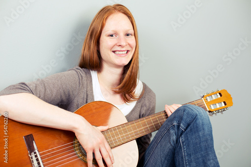 Happy woman with a classical guitar smiling at the camera