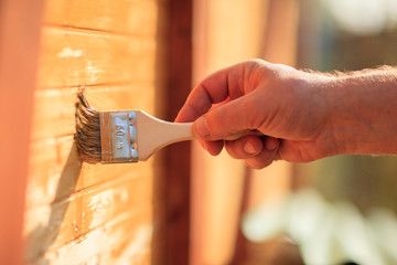 Hand painting wooden wall paint with brush