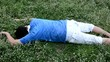 An Asian guy is drop dead on the grassy ground