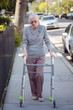 Senior woman walking with walker on city street