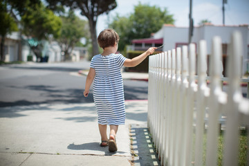 Girl walking next to fence