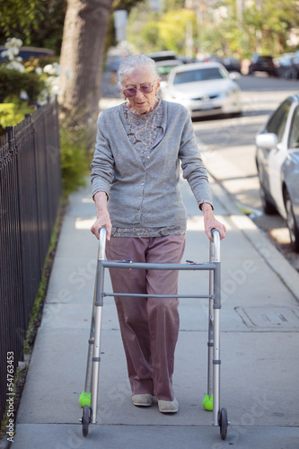 Senior woman walking with walker on city street