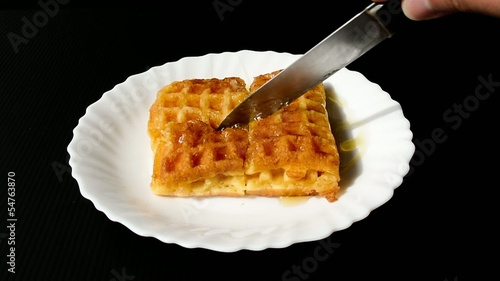 baked waffle topped with honey syrup is cut into pieces