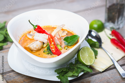 Traditional spicy Thai Tom Yam soup on a wooden table