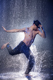 Dancing in the rain. Young male dancer in black fedora dancing i