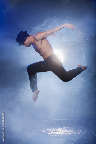 Wet dancer. Young male dancer in black fedora dancing on the wet