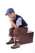 Kind sitzt auf Koffer