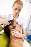 woman having a stimulating facial treatment from a therapist poster