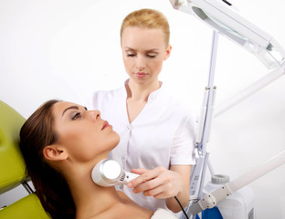 woman having a stimulating facial treatment from a therapist