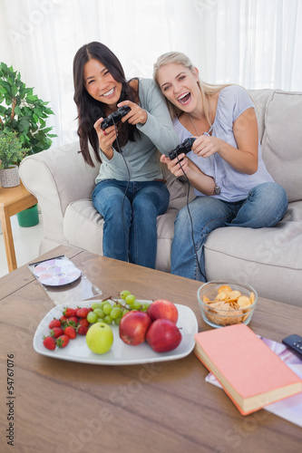 Happy friends playing video games and laughing