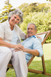 Smiling mature couple resting on sun lounger