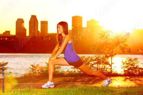 Woman runner stretching legs after running