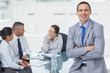 Smiling businessman posing while workmates talking together