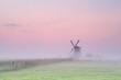 windmill on meadow in morning fog