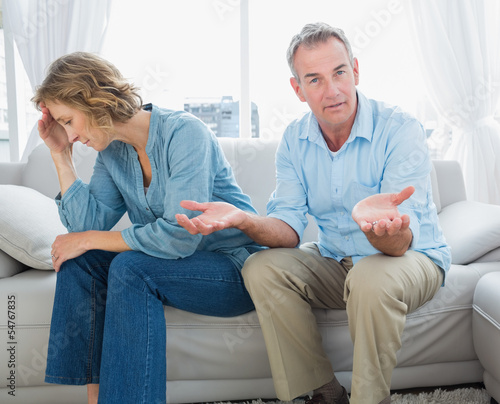 Arguing middle aged couple sitting on the couch with man gesturi