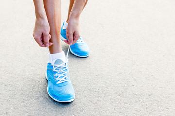 Closeup of Young Woman Tying Sports Shoe
