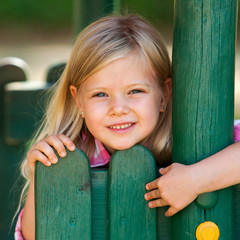 Cute girl holding on to wooden fence.