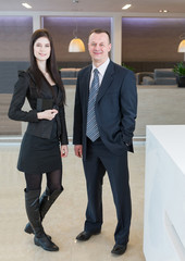 Man and woman in business suits standing at reception