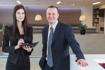 Man and woman standing at reception with notepad