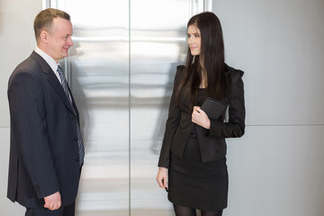 Man and woman in business suits waiting for elevator