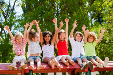 Happy kids raising hands outdoors.