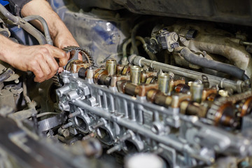 Hands of automechanic, who repairs car engine