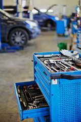 Blue metal tool cabinet with open case at service station