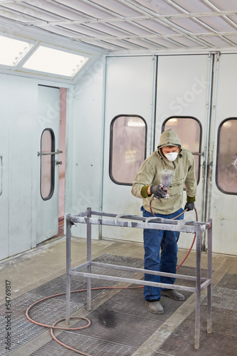 Man in protective clothes and respirator works in paint-spraying