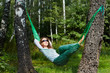 Young smiling woman in dark sunglasses lies in hammock