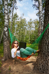 Young barefooted woman in dark sunglasses lies in hammock