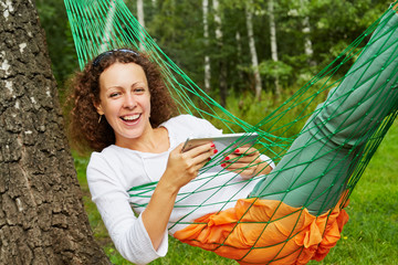 Young smiling woman lies in hammock with tablet PC outdoors