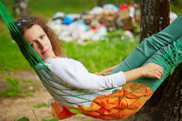 Young woman with discontented face lies in hammock at birchwood
