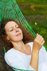 Young woman lies in hammock and looks at yellow flower she holds