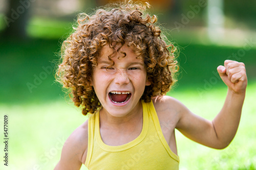 Shouting boy pulling fist up.