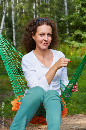 Young smiling woman sits in hammock with yellow flower